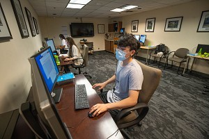 study at computer wearing face mask